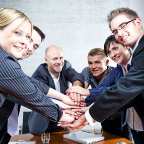 Group of business professionals with hands together.